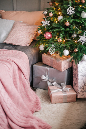 decorations on the Christmas tree with pink balls and a plaid on the bed