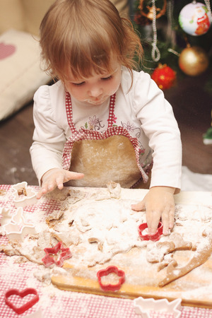 children in an apron are cooking gingerbread cookies in the kitchen