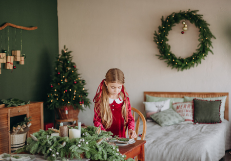 girl in a burgundy dress decorates a Christmas tree in a rustic room Фото со стока