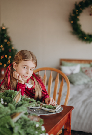 girl in a burgundy dress decorates a Christmas tree in a rustic room 版權商用圖片