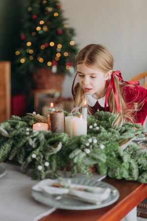 girl in a burgundy dress decorates a Christmas tree in a rustic room Stock fotó