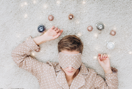 girl in beige pajamas and a sleep mask lies sleep with Christmas decorations balls golden gray