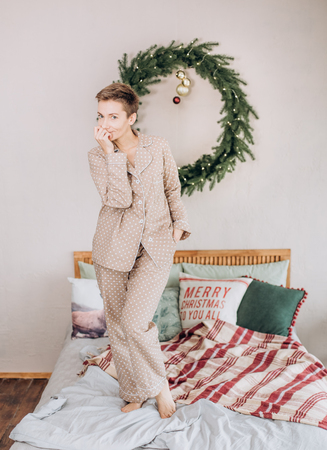 girl in pajamas in the bedroom on the bed with a Christmas wreath 写真素材