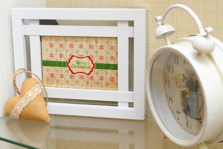 Christmas card in a white frame on the shelf with the decor of the clock and heart
