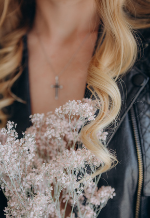 girl blonde in a leather jacket with flowers in the style of rock