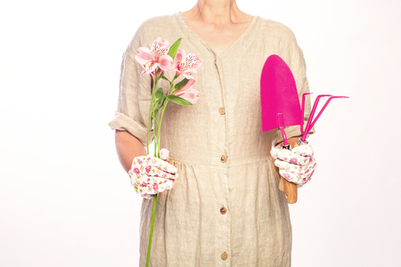 women with gardener tools pink colored holding a bouquet of flowers