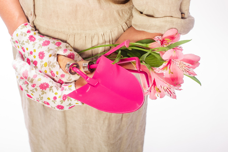mujeres con herramientas de jardinero de color rosa sosteniendo un ramo de flores