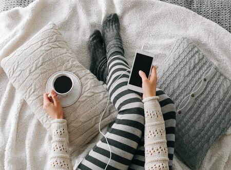 girl in home clothes with a smartphone and a cup of coffee on the bed Stockfoto