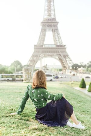 female tourist looks at the eiffel tower sitting back on the grass lawn