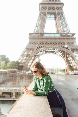 french manicure woman with smartphone against the background of the eiffel tower and reflection in glasses