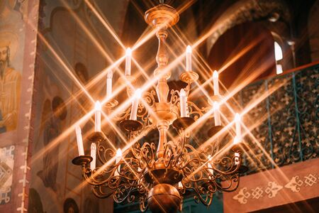 antique gold chandelier with a group of glowing candles with highlights in the temple