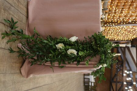 festive decor of a banquet hall with garlands of gold and floral design in a rustic style