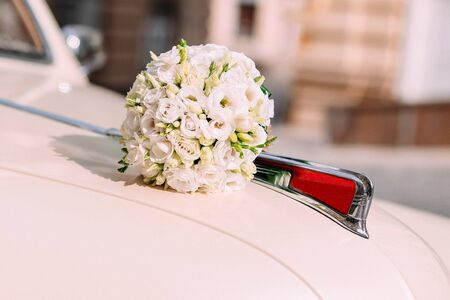 wedding bouquet on the hood of a white retro car outside Reklamní fotografie