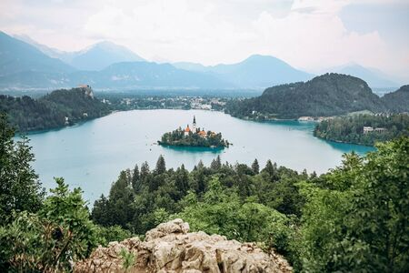 island with prayer cathedral on bled lake and mountains on background Stock Photo