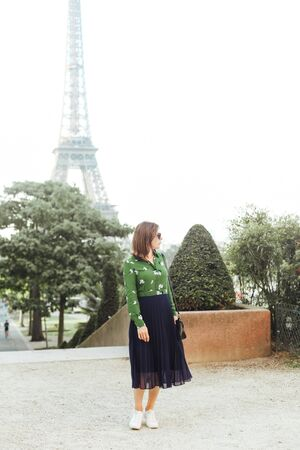 Portrait of a stylish woman on the background of the Eiffel Tower in Paris