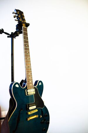 shiny electric guitar on a stand on a white background