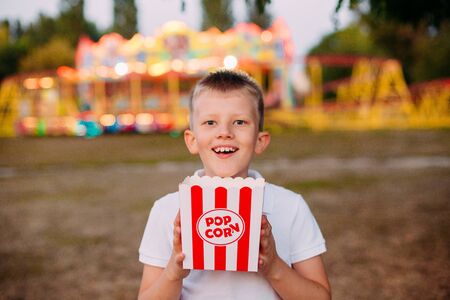 serving popcorn in hands of a child festival fair with colorful background in blur Фото со стока - 132168605