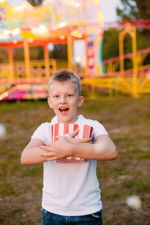 Popcorn and child festival fair with colorful background in blur Фото со стока
