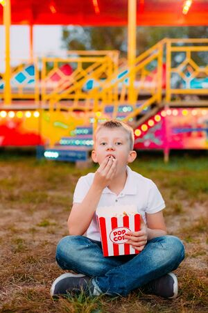 popcorn and a child sitting on the steps of a carousel outside a festival fair with a colorful background