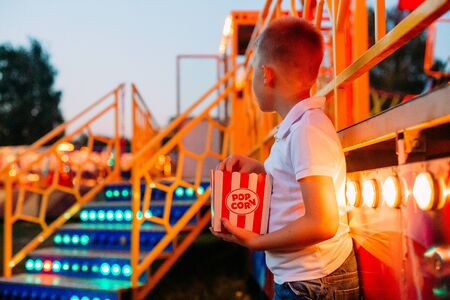 popcorn and child eating outside festival fair with colorful background Фото со стока - 132168609