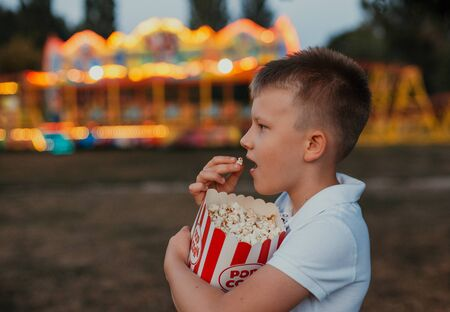 serving popcorn in the hands of a child eating outside a festival fair with a colorful background