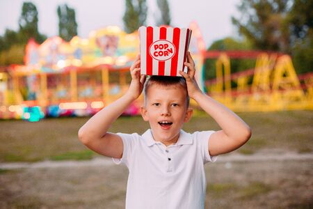 serving popcorn on the head joy and emotions child outside festival fair with colorful background Фото со стока - 132166861