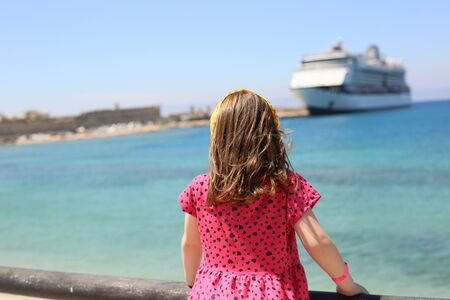 little girl outside in a red dress looks cruise liner moored on a pier