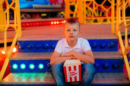 popcorn and a child sitting on the steps of a carousel outside a festival fair with a colorful background Фото со стока - 132165804