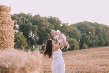 autumn conceptual mother with a small daughter in white dresses on a field with a straw 写真素材