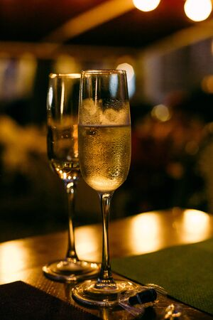 two glasses with champagne on a holiday background with garlands