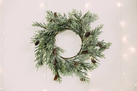 elegant coniferous wreath and bumps with garlands decorated on a white wall