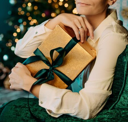 gifts boxes with gold black ribbons in the hands of a woman on the background of a Christmas tree in the bokeh of garlands