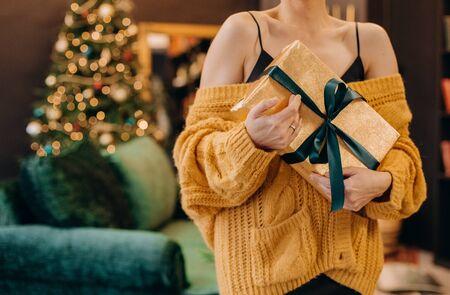 gift in the hands of a girl on the background of the New Year interior and Christmas tree Фото со стока