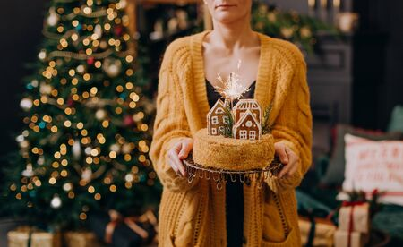 New Year woman in a festive interior with garlands of Christmas trees and gifts