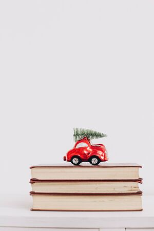 Christmas toy red car with a Christmas tree on the roof stands on books isolated