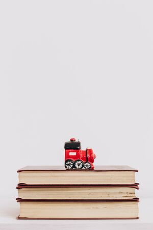 Christmas toy red retro locomotive stands on books isolated
