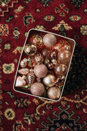 Christmas decorations balls pink powdery shape patterned in a box on a red carpet Фото со стока
