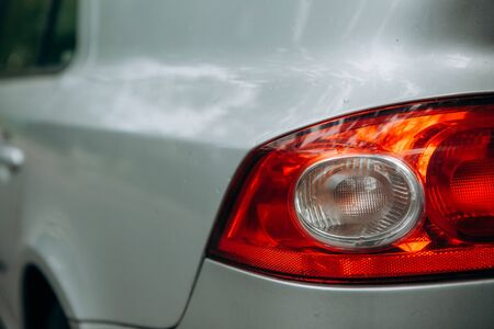 red taillight of a gray car with drops of water after washing Banque d'images