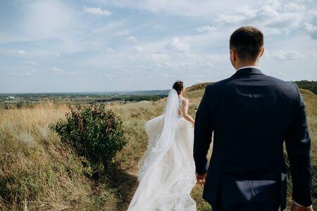couple in love wedding together outside field path landscape sky veil wind freedom Фото со стока