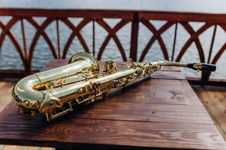 saxophone glitters outside on a wooden table promenade cafe terrace