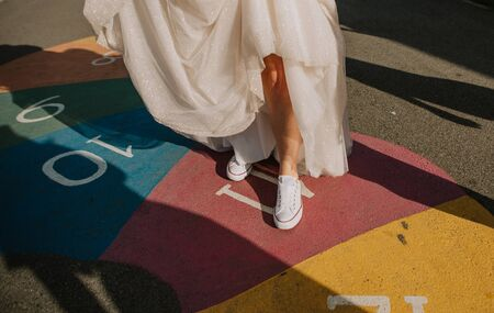 bride in a white dress and shoes sneakers jumping playing on the pavement classics game with colored numbers