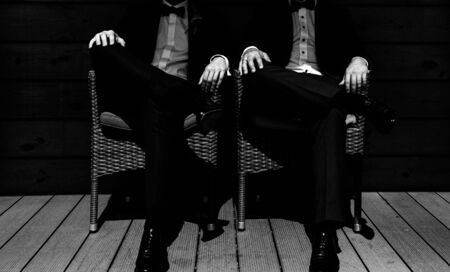 two men sit pose synchronously in suits classic style