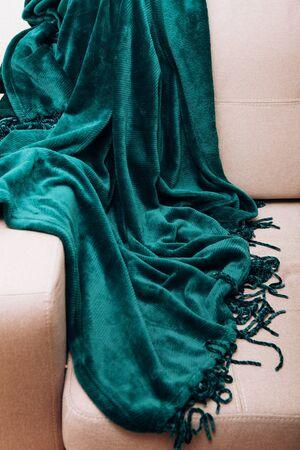 green velvet warm plaid beautifully draped on a gray sofa Фото со стока