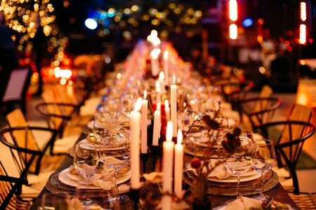 long festive table with candles and bokeh bright garlands in the background