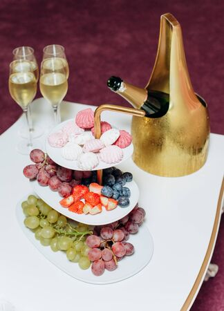 fruit grapes marshmallows colored table set festive champagne ice gold background garland blur light bright