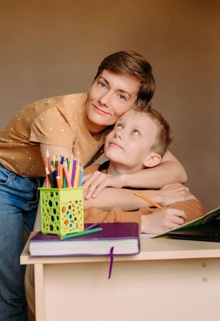 home online learning school mom helping son do homework and fatigue Archivio Fotografico