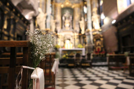 white flowers on a bench in majestic architecture of the catholic cathedral inside with columns