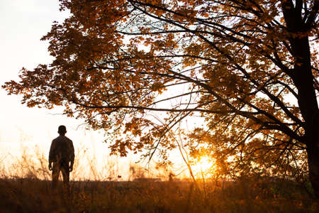 man stands at sunset with magic light in the forest autumn season fallen leaves