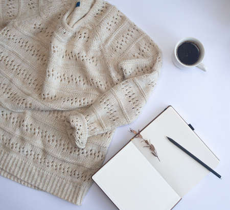 warm knitted wool sweater winter mock up with objects notepad pencil and cup of coffee