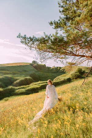 woman in white dress with wings outside meadow runs to freedom back view